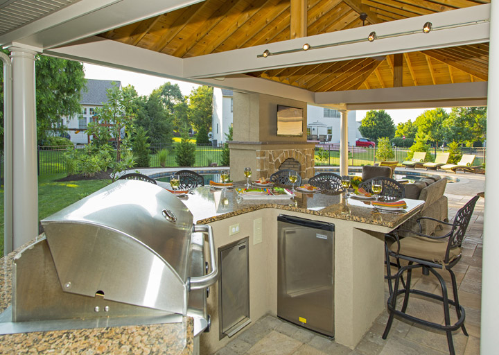 outdoor kitchen with multiple appliances and guest seating