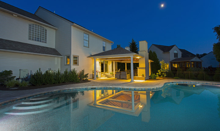 pool and pavilion with outdoor lighting and fireplace in Lancaster, PA