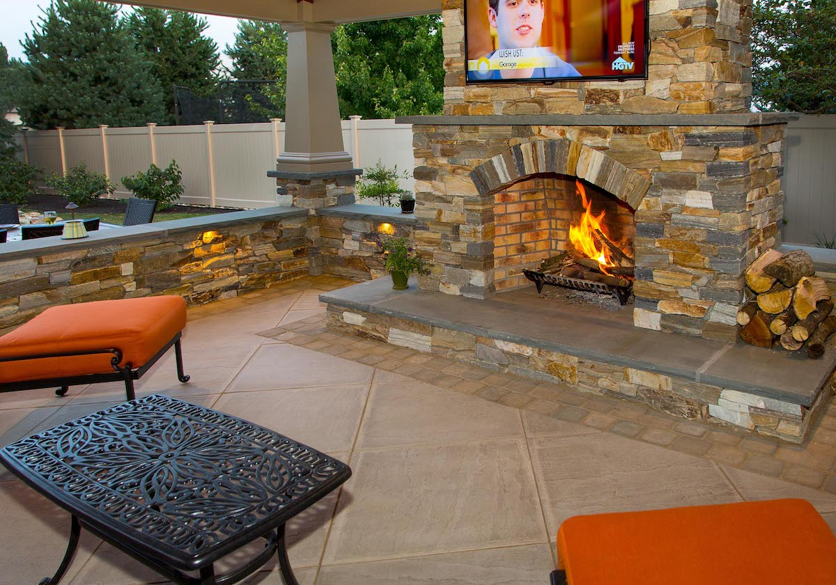Natural stone outdoor fireplace with television in New Holland, PA