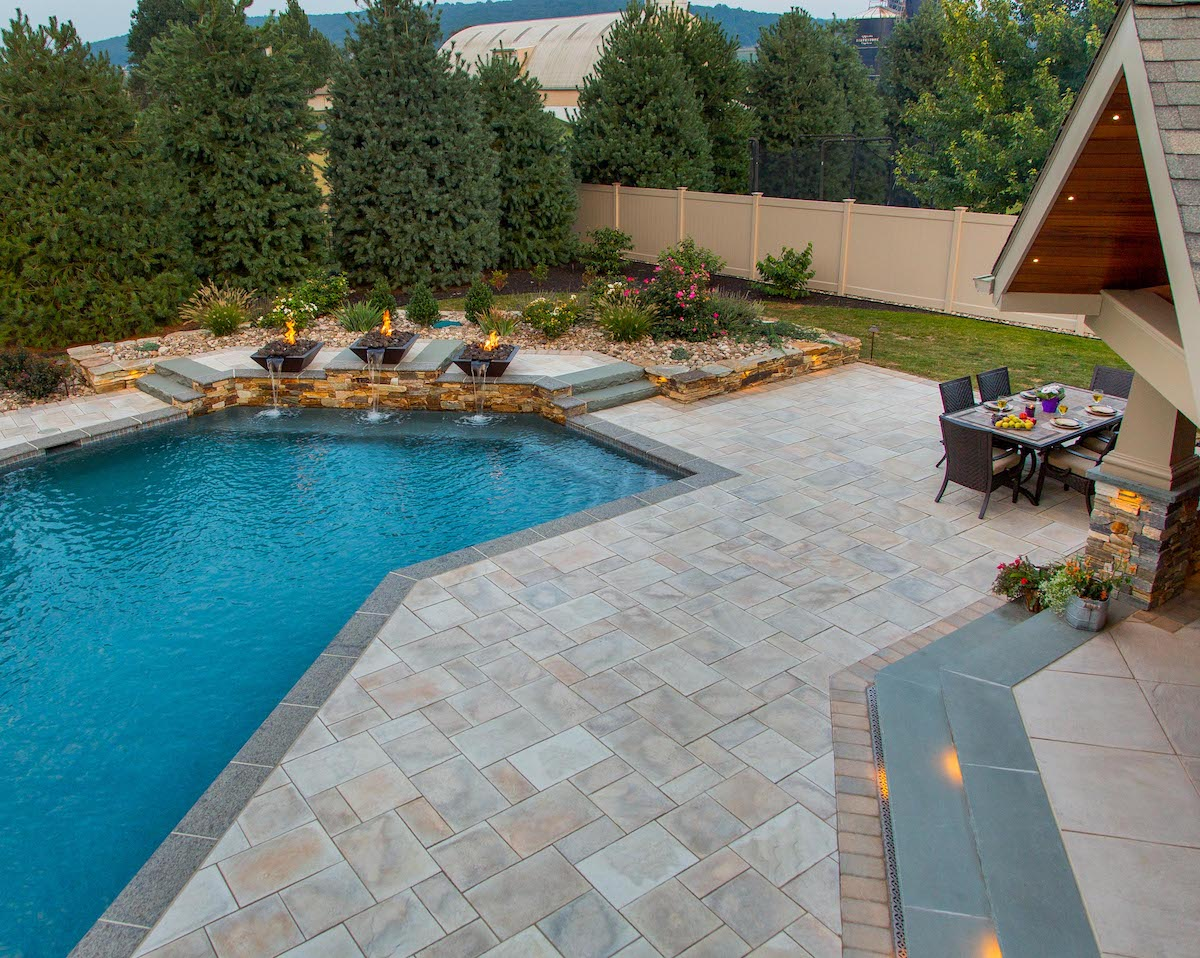 Pool patio with pavers and fire bowl fountains