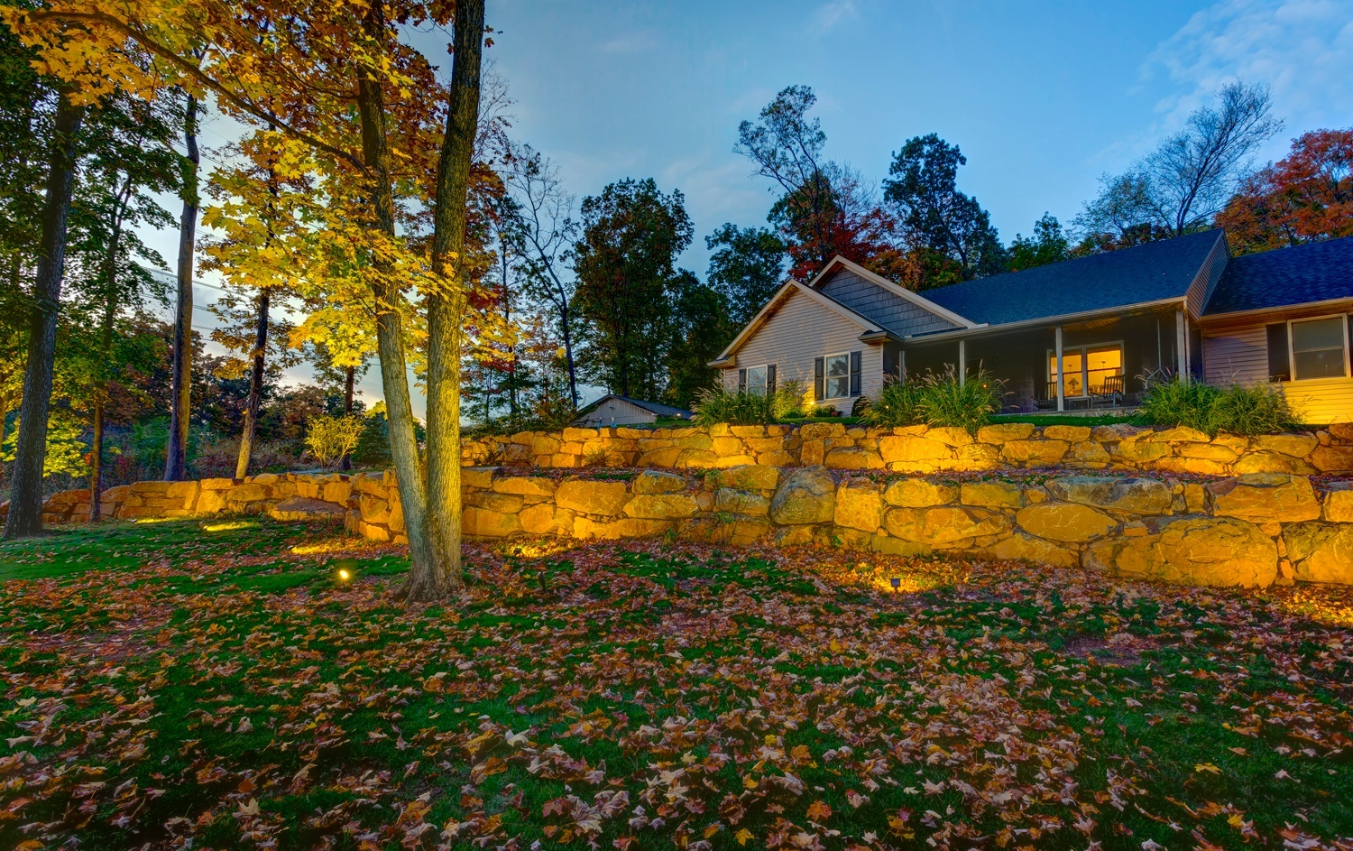 Boulder wall in front yard with landscape lighting