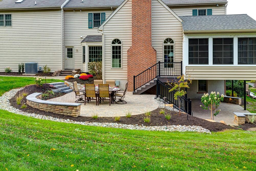 house with patio under deck and sloped yard