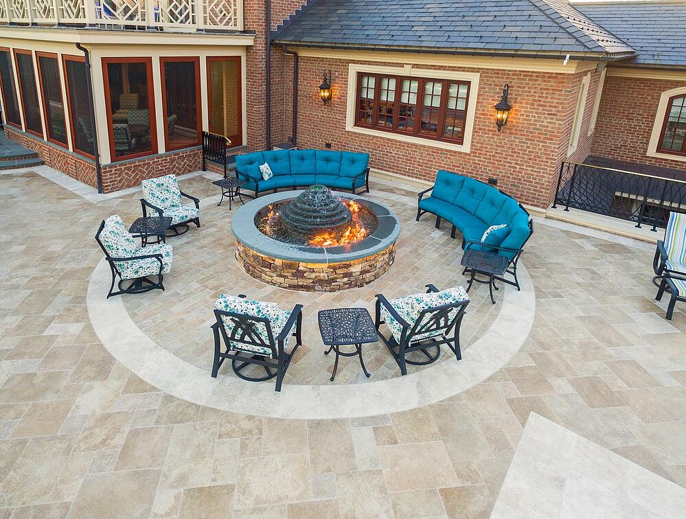 large fire pit fountain on patio with chairs for guests