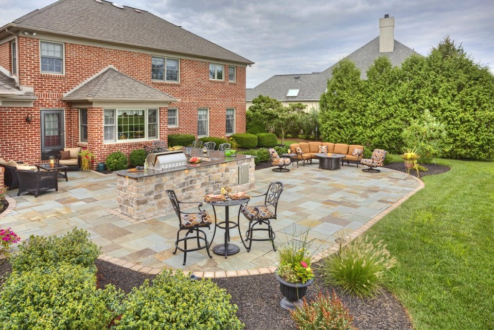 Flagstone patio, outdoor kitchen, and plantings designed by Earth Turf & Wood