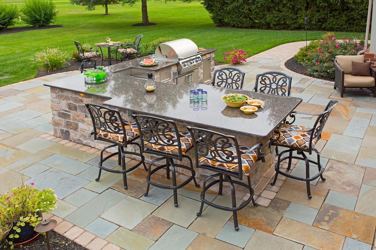 Outdoor kitchen and seating on flagstone patio designed by Earth Turf & Wood