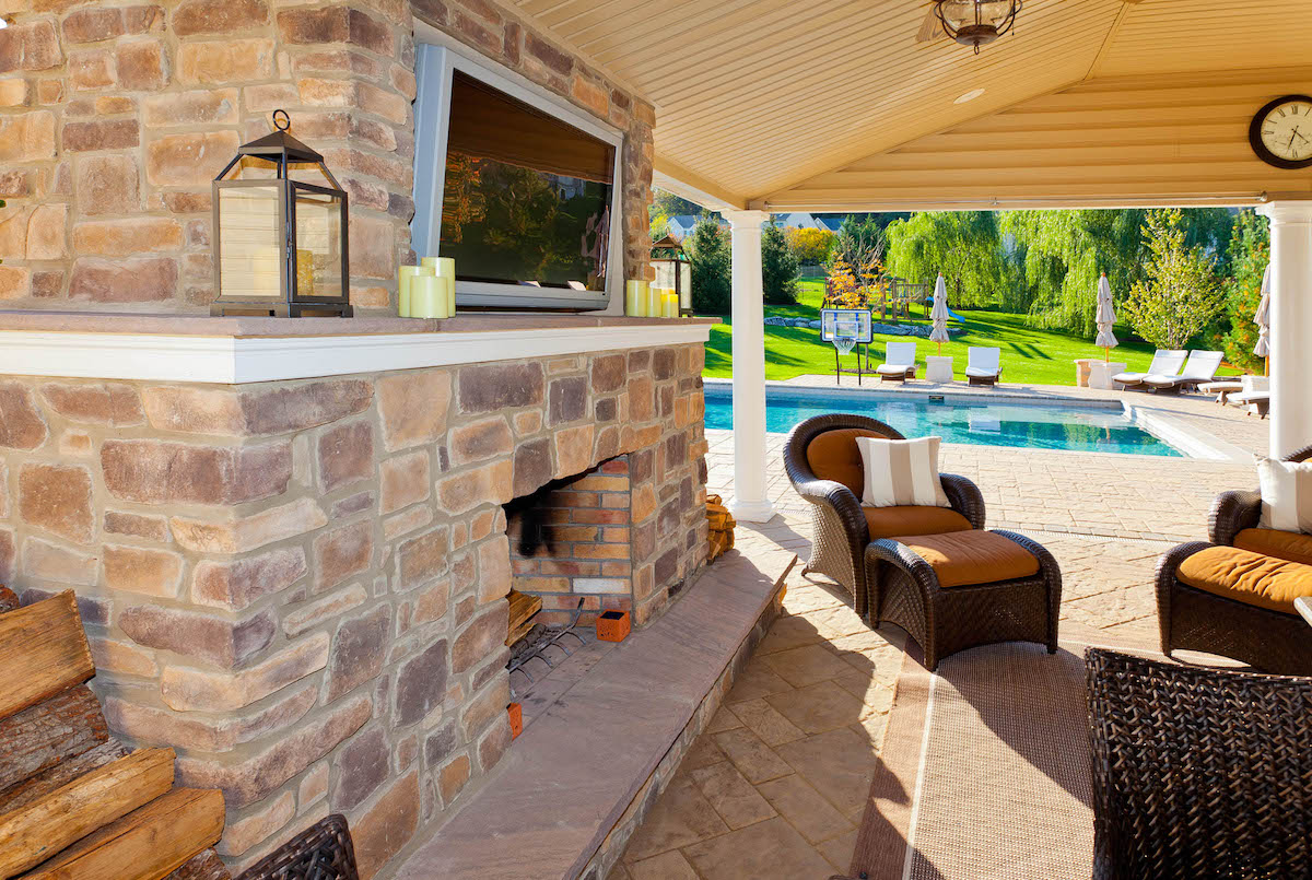 Pavilion with outdoor fireplace, TV, and pool