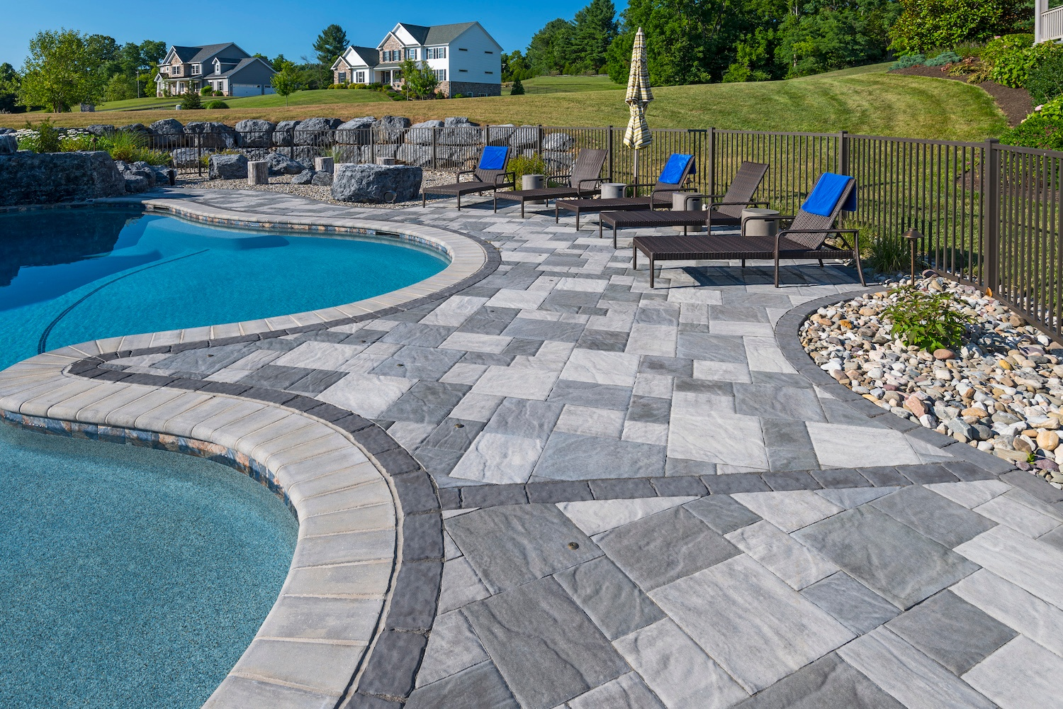 Pool patio with pavers and boulders