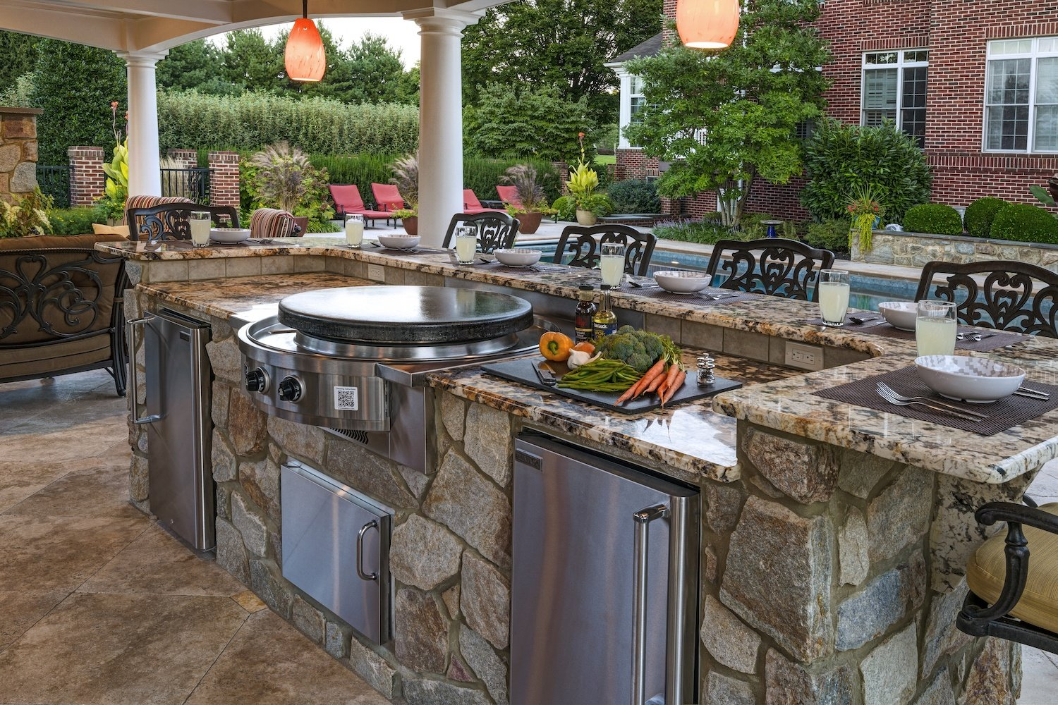 outdoor kitchen appliances and bar overlooking pool