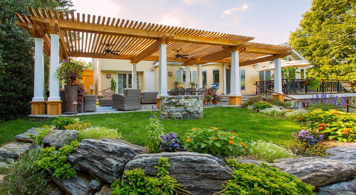 Landscape with pergola, plants, and fire pit in Leola, PA