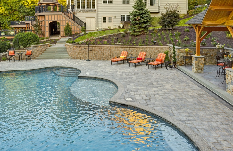 Pool patio with pavilion, steps, and retaining wall