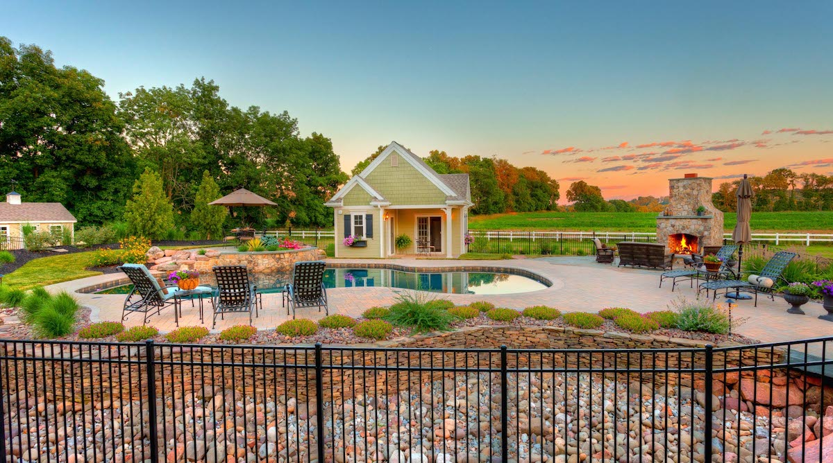 Pool with poll house, outdoor fireplace, and landscaping