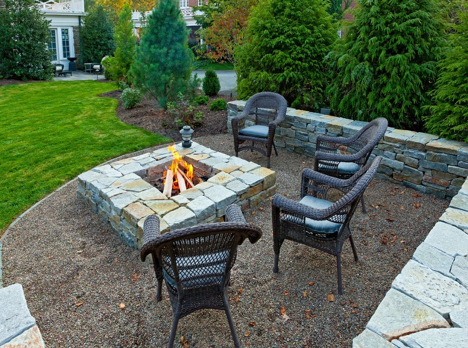 square stone fire pit and wall on gravel