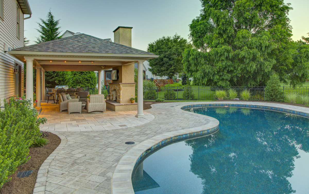 beautiful pool, pavilion, and outdoor fireplace designed by landscaping company