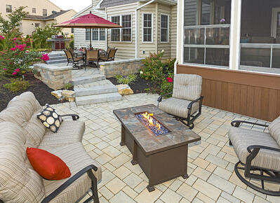 Home patio landscape with fire pit, pavers, and shrubs