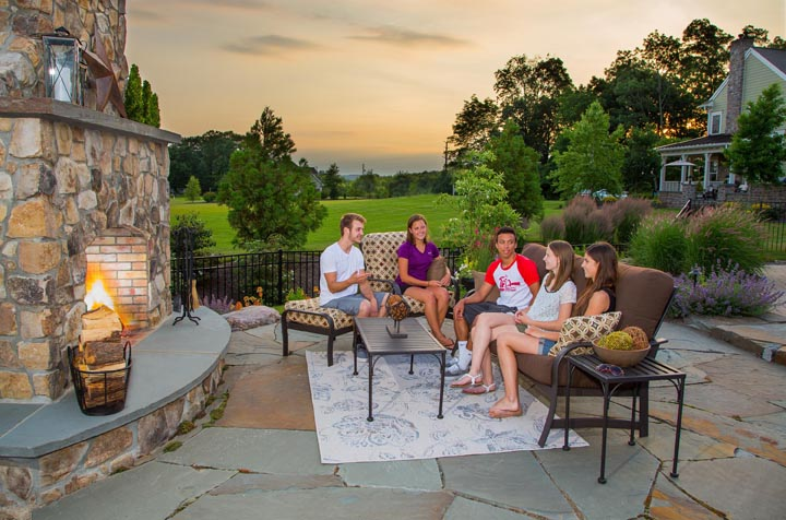 people enjoying patio with outdoor fireplace