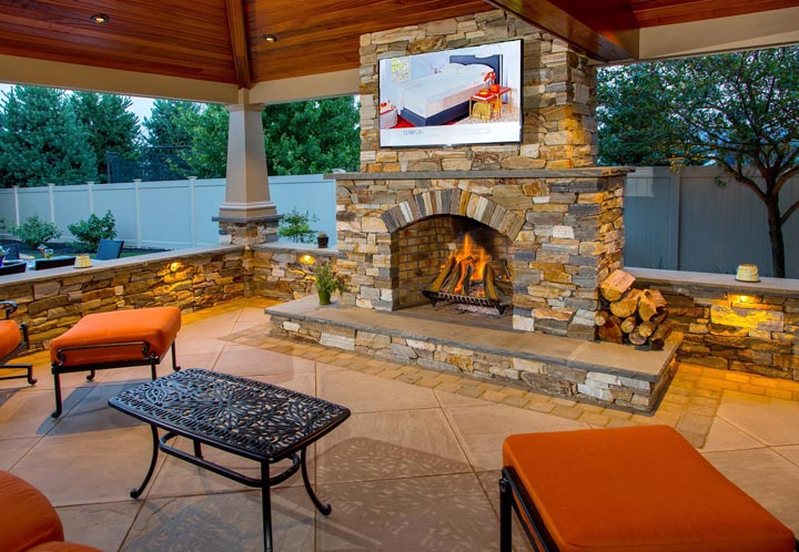 outdoor stone fireplace under pavilion with television