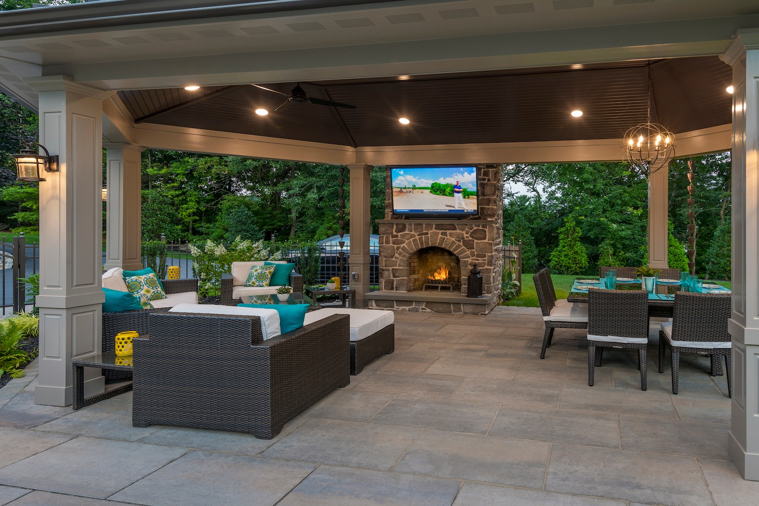 backyard pavilion with fireplace, tv, and dining area