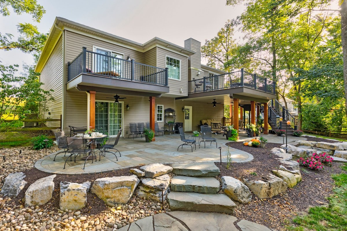 home with 2 decks, flagstone patio, and boulder wall