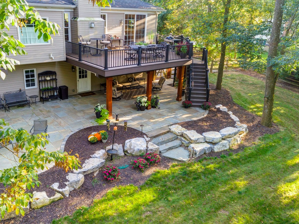 large deck with flagstone patio and sloped backyard