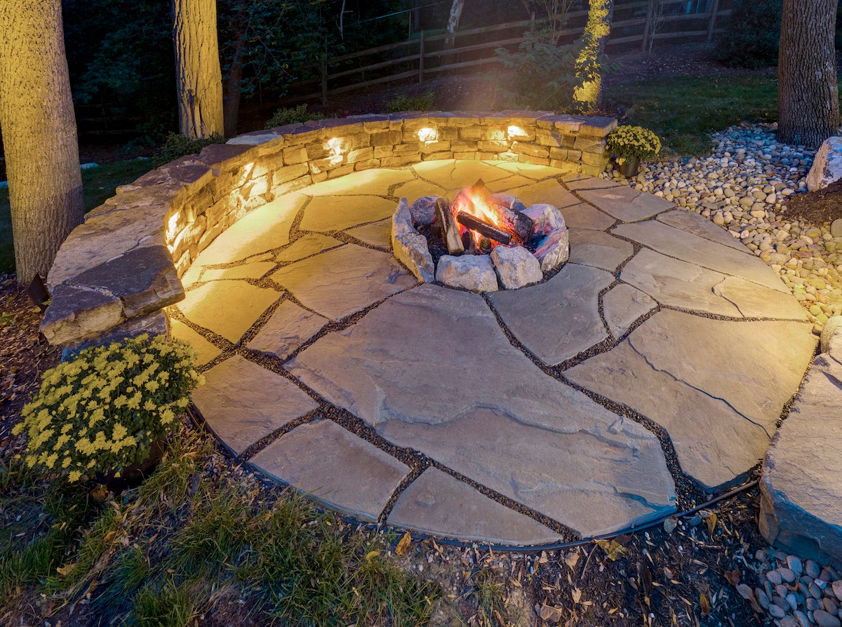 flagstone patio and wall with lighting and fire pit