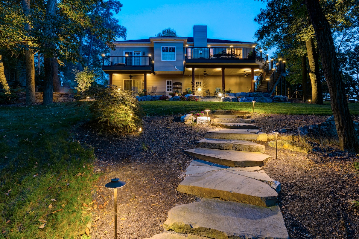 sloped backyard with steps and landscape lighting
